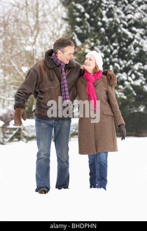 Älteres Paar zu Fuß In Schneelandschaft - Stockfoto