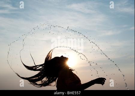 Indische Mädchen werfen ihr nasses Haar zurück verursacht Wasser Spray Silhouette. Indien - Stockfoto