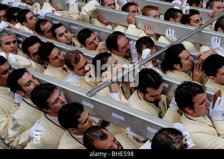 Etwa 250 spanische Männer, die Mitglieder der Bruderschaft, tragen während der Karwoche in Malaga, Spanien, einen - Stockfoto