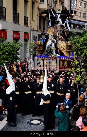 Der große Thron mit der Paso-Szene wird während der Karwoche in Málaga, Spanien, in einer engen Straße getragen. - Stockfoto
