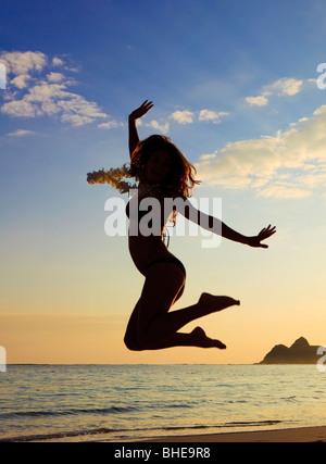 Silhouette einer jungen Frau laufen und springen am Strand von hawaii - Stockfoto