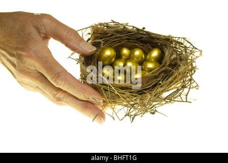 Ältere Frau für Vogelnest mit kleinen goldenen Eiern, Studio gedreht zu erreichen - Stockfoto