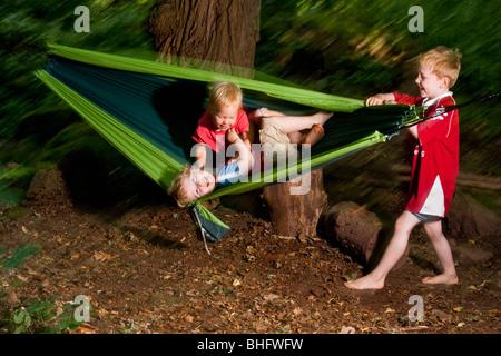 Zwei Jungs und ein Mädchen spielen in einer Hängematte, Pfalz, Deutschland - Stockfoto