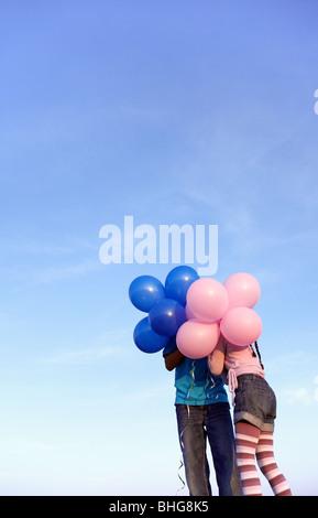 Zwei Kinder hinter Luftballons - Stockfoto