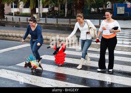 Junge Spanierin in Flamenco-Kleid mit Hund an der Leine im Kostüm unterwegs Ther zum Karneval in Las Palmas auf Gran Canaria.