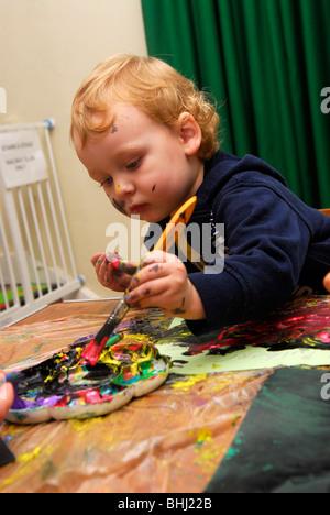 2 Jahre alte junge Malerei Bild in einem Gemeindezentrum Tag der offenen Tür für Kinder während der Schulferien - Stockfoto