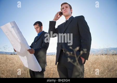 2 Männer mit Plänen im Feld, auf Handy - Stockfoto