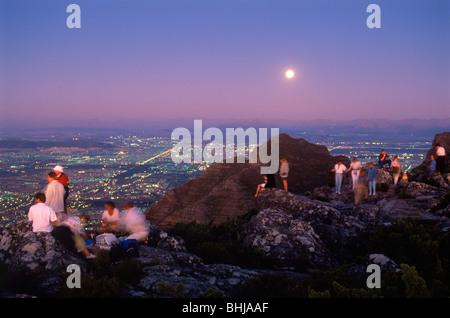 Besucher mit Speis und trank Sonnenuntergang von oben auf den Tafelberg über Kapstadt unter Vollmond - Stockfoto