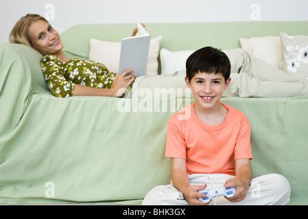 Kleiner Junge sitzt am Boden spielen Videospiel, Mutter entspannend auf sofa - Stockfoto