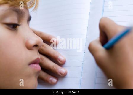 Preteen Mädchen schreiben in notebook - Stockfoto