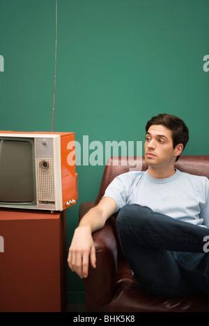 Mann sitzt im Stuhl, ungeduldig wegschauen - Stockfoto