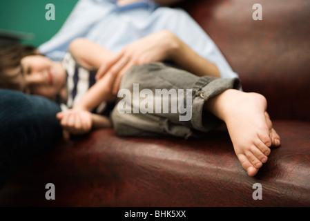 Kleiner Junge mit Kopf in des Vaters Schoß ruhen - Stockfoto