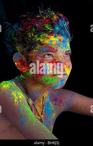 Glücklichen jungen bedeckt Farbpulver Pigment vor schwarzem Hintergrund - Stockfoto