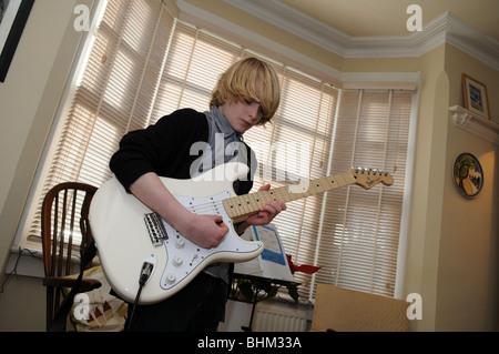 Teenager-Jungen üben den Blues in seinem Wohnzimmer auf einer Creme Fender Stratocaster-Gitarre, umrahmt von einem - Stockfoto