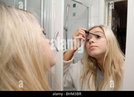 Blonde Teenager-Mädchen auf ihre Wimperntusche spiegelt sich in ihrem Badezimmerspiegel, UK - Stockfoto