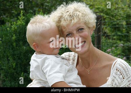 Mutter halten Baby in Händen Porträt glücklich Lachen blond - Stockfoto