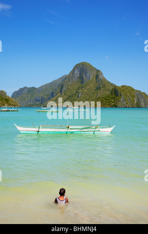 Junge sitzt im Meer Banca Boot und Cadlao Insel zu betrachten; El Nido; Bacuit Bay; Palawan; Philippinen. - Stockfoto