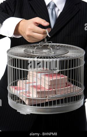 Geschäftsmann hält Vogelkäfig mit Geld gefüllt - Stockfoto