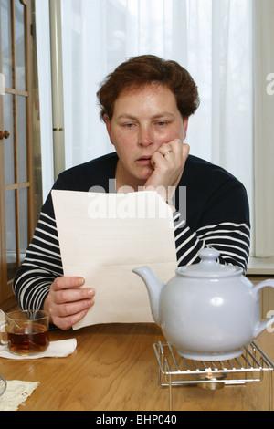 Erwachsenen plus Größe Frau liest Papier Dokument sitzen am Tisch und sorgen. - Stockfoto