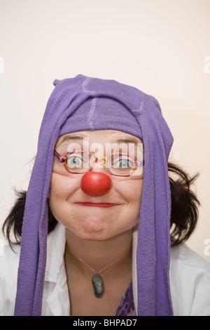 Clown-Doktor: Clown mit roter Nase und Strumpfhose auf dem Kopf mit törichten Ausdruck in ihrem Gesicht. - Stockfoto