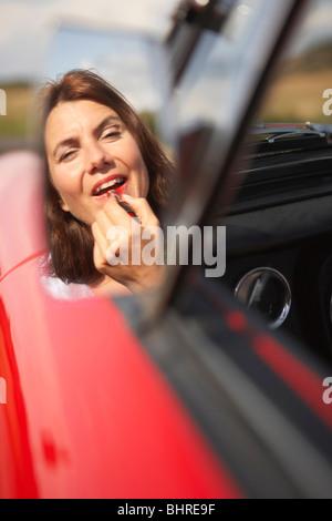 Frau Auftragen von Lippenstift in Autos Spiegel - Stockfoto