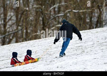 Vater ziehen zwei Kleinkinder bergauf auf Schlitten in Cherokee Park in Louisville - Stockfoto