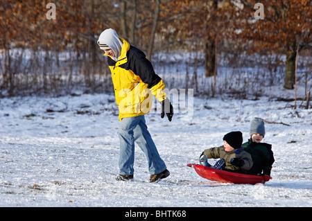 Vater ziehende zwei jungen auf Schlitten in Cherokee Park in Louisville, Kentucky - Stockfoto