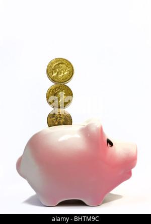 Pfund-Münzen und rosa Sparschwein - Stockfoto