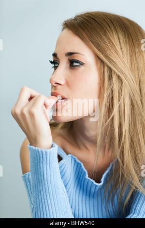 Porträt der 30 Jahre alte Frau beißen ihre Fingernägel auf Cyan Hintergrund. Vertikale Form - Stockfoto