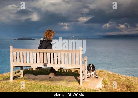 Mutter Ivey Bay; Walker auf Bank ausruhen; mit Blick auf Tintagel; Cornwall - Stockfoto