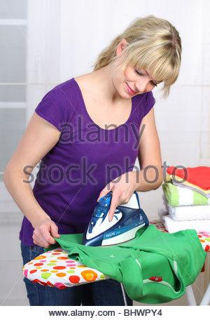 junge Frau, die gerne ihre Kleidung bügeln - Stockfoto
