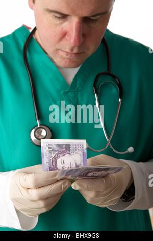 Mann trägt medizinische Peelings und Stethoskop 20 Pfund Sterling Banknoten zählen - Stockfoto