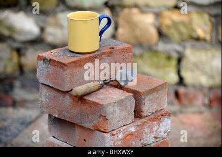 Ein Baumeister Becher Tee auf einem Stapel von aufgearbeiteten roten Ziegeln UK - Stockfoto