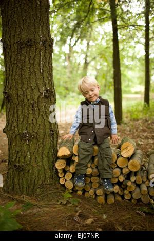 Junge sitzt auf einem Stapel Holz. Stockfoto