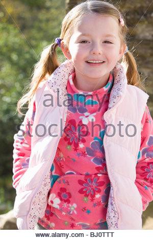 Lächelndes Mädchen mit Weste im freien - Stockfoto