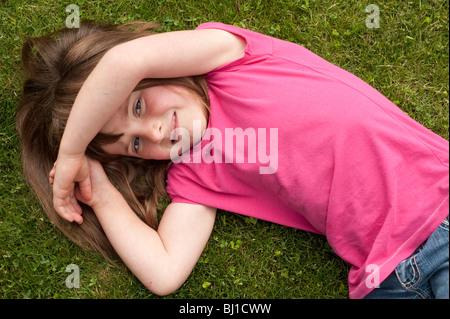 kleines Mädchen (5 Jahre alt) Verlegung in den Rasen - Stockfoto