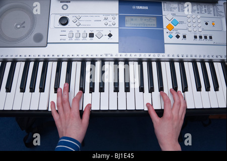 Ein MODEL Release Bild eines 10 Jahre alten Jungen spielen auf seinem Keyboard im Vereinigten Königreich - Stockfoto
