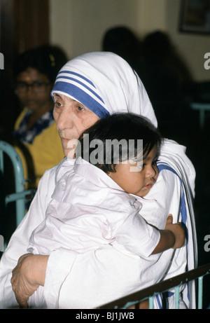 Mutter Teresa von Kalkutta schmiegt sich ein Kind in ihrer Mission zur Unterstützung der armer und hungernder Menschen, - Stockfoto