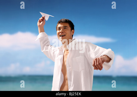 Mann spielt Papierflieger am Strand, Lächeln - Stockfoto