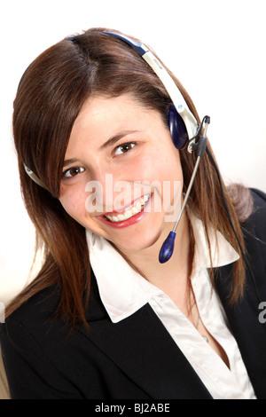 Junge Frau in einem Callcenter. Sie trägt einen Kopfhörer und lächelt in die Kamera - Stockfoto