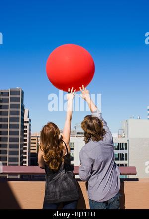Freunde auf dem Dach mit roten Ballon - Stockfoto