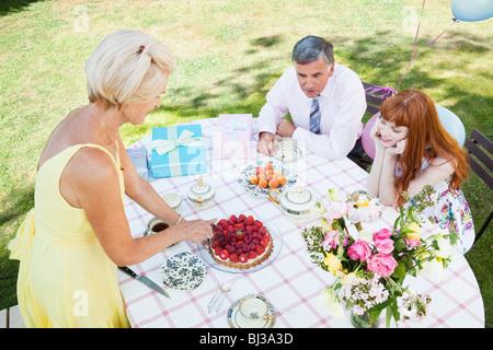 Frau schneiden Kuchen während andere schauen auf. - Stockfoto