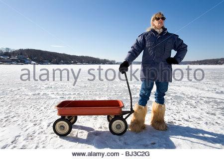 Frau steht neben ihr Radio Flyer Red Wagon auf zugefrorenen See im Winter. - Stockfoto