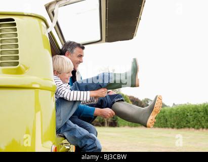 Vater und Sohn setzen auf Stiefel - Stockfoto
