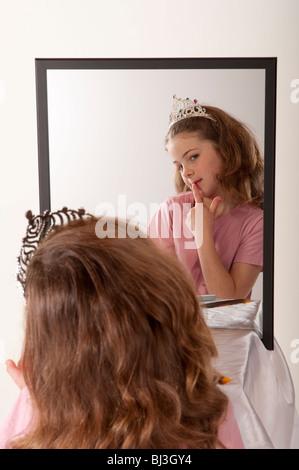 kleines m dchen betrachtet sich im spiegel w hrend des. Black Bedroom Furniture Sets. Home Design Ideas