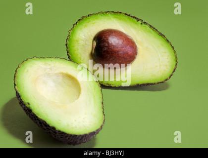 Hass Avocado Sorte Birne in Scheiben geschnitten in zwei Hälften auf einem grünen Hintergrund.