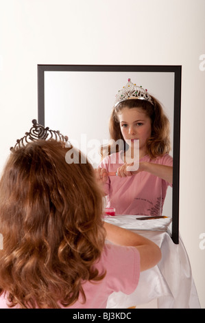 kleines Mädchen betrachtet sich im Spiegel während des Spielens Make-up und Märchen Prinzessin - Stockfoto