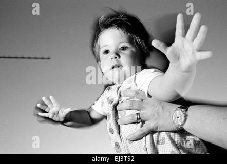 Ein elf Monate altes Kind steht auf einem Tisch im Restaurant und wird von ihrer Mutter gehalten, während Ihres - Stockfoto