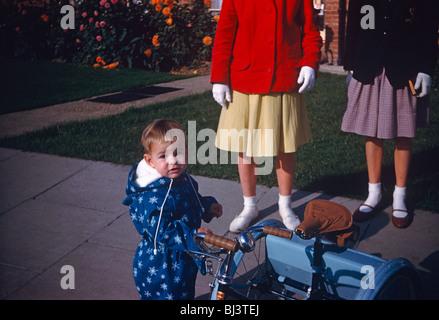 Ein kleiner Junge trägt einen blauen Sprunganzug hält den Lenker eines Favoriten passenden blauen Dreirad mit 60er - Stockfoto