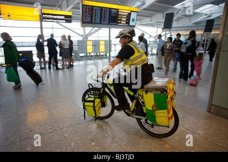 NHS Sanitäter Janet Greenhead durchläuft die Abfahrten Bahnhofshalle auf ihr Mountainbike spezialisiert Rockhopper - Stockfoto